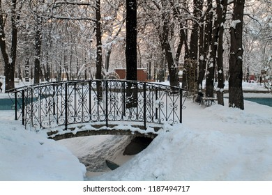 Arched iron bridge covered with a high snowdrift. The bridge in the form of an arch in a winter park is covered with white snow.