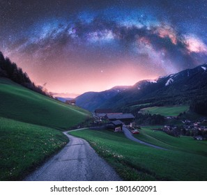 Arched Milky Way over the rural mountain road in summer in Italy. Beautiful night landscape with starry sky, milky way arch, winding road in mountain village, hills, green meadows and buildings. Space