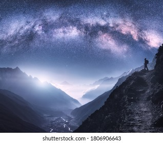 Arched Milky Way, woman and mountains at night. Silhouette of standing girl on the mountain peak, mountains in low clouds and starry sky in Nepal. Space landscape with purple milky way arch. Travel