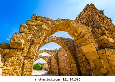 Arched passage - covered street of Port of Caesarea. Sunny spring day. Ruins of the ancient city of Caesarea. Israel. Concept of ecological and historical tourism