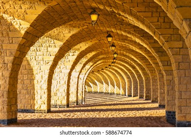 The arched stone colonnade with suspended lanterns