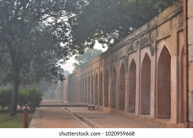 Arched walls beautiful architecture of Humayun's Tomb in Delhi looking like an endless trail with trees on one side