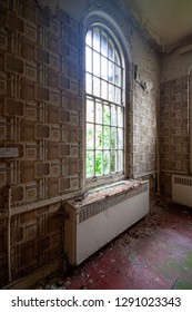 Arched window in room at an abandoned and derelict lunatic asylum/hospital (now demolished), Cane Hill, Coulsdon, Surrey, England, UK