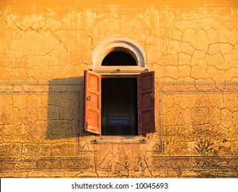 Arched window with shutters in decorated wall of ancient Palace in Rajasthan, India
