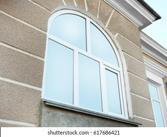 Arched window with tinted glass on grey wall background