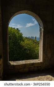 Arched window without glass with a view of the sea and trees