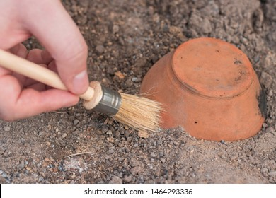 archeology . Male hand holding brush. brush; excavation of rare pots and villages. tools for the excavation and culture of ancient settlements and caves. Elements of Culture BC