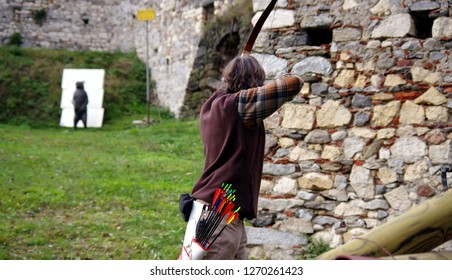 archer bending his bow toward a target