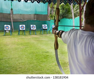 Archer man pulls the bowstring and arrow, aiming at a target