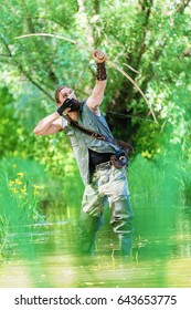 Archer man shooting the bow and arrow in the swamp