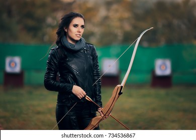 Archer Woman with Bow and Arrow in Target  Training  - Cool cosplay girl wearing leather jacket in archery practice