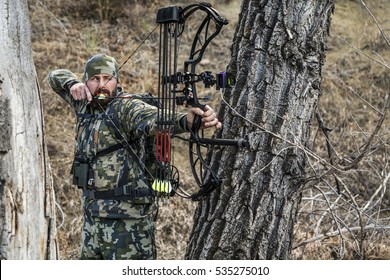 archery hunter with his bow drawn back ready for a shot