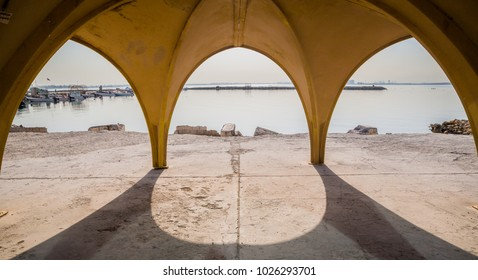 Arches hold up a pavilion near the sea.