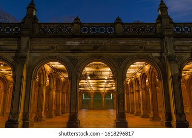 Arches leading into the Bethesda Arcade in New York City's Central park at night.