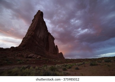 Arches National Park Courthouse Tower and sunset alpenglow in the Spring.  Clouds and rain are common in the springtime near Moab, Utah and surrounding desert of the Colorado Plateau.