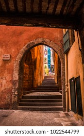 Arches in Villefranche-sur-mer with orange wall in narrow path through the town, France
