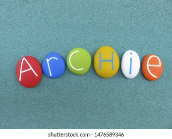Archie, masculine given name composed with multi colored stones over green sand