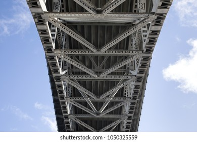 An arching lattice structure made of geometric iron beams, under a large arching bridge, with a cloudy blue sky background
