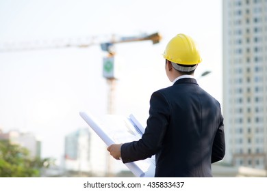 Architect with blueprint at skyscrapers background