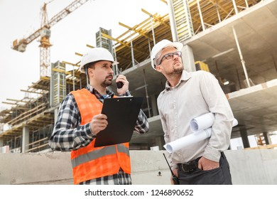 Architect with blueprints and developer and a safety vest and walkie talkie at construction site. Development and construction industry concept