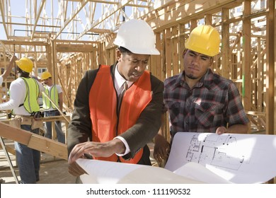 Architect and builder discussing at construction site