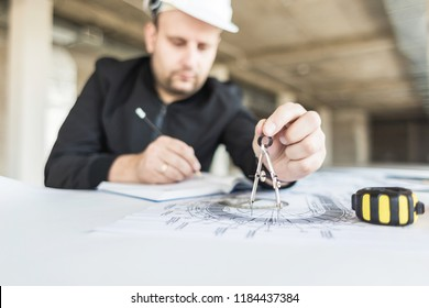 architect builder works at the table with drawings. Helmet, drawings, compasses in the workplace