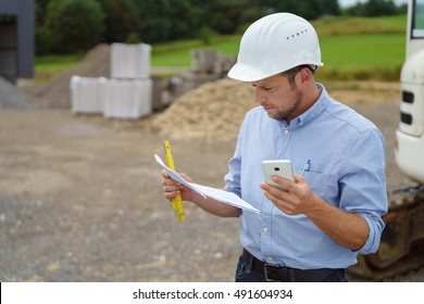 Architect or building contractor working on site standing reading a document in his hard hat with a mobile in his hand , with copy space