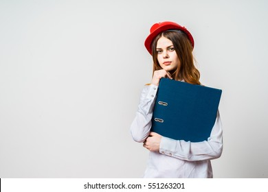 Architect business woman standing against white wall with blue folder in hands. Young smiling woman. Building helmet.Copy space