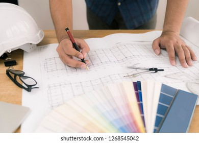 architect or civil engineer during drawing home or building in office on working table with office stationary , laptop ,color pallette sampling.