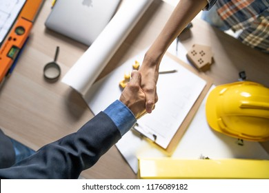 Architect or civil engineer and house owner shaking hands after house finish or discuss about home drawing on working site.