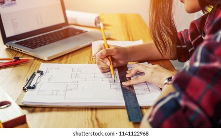 Architect concept, Architects working with blueprints in the office, hand working and laptop with on on architectural project at construction site at office desk in office