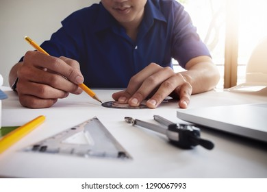 Architect or construction design concept. Young engineer working in office and using computer laptop, blueprint to design house or building. Engineering concept.
