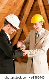 Architect and construction engineer or surveyor shaking hands, Both are wearing hardhats and are standing on the construction site of a home indoors
