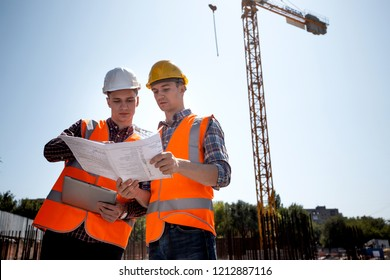 Architect  and construction manager dressed in orange work vests and helmets discuss documentation on the open air building site next to the crane