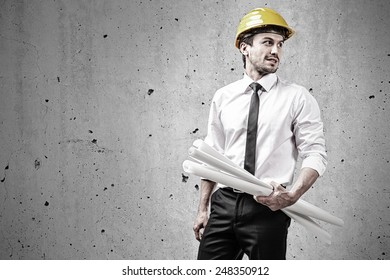 Architect at construction site holding plans in front of a concrete wall