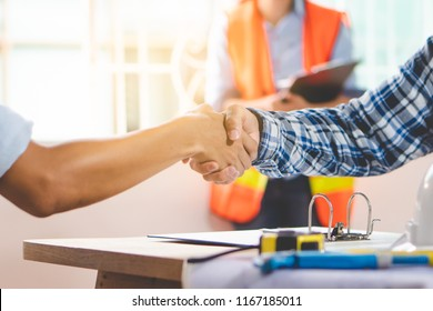 Architect contractor shaking hands with client after seal a deal to renovate building.