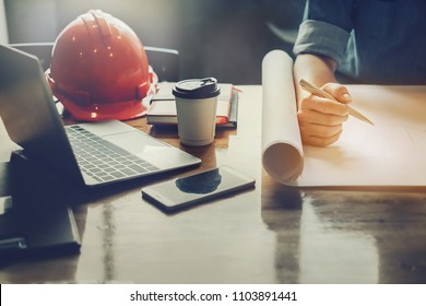 architect design concept, Engineering hand holding pencil design building on blueprint of drawing in job site with helmet and laptop computer.