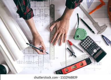 Architect is designing blueprints for home construction.