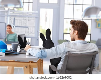 Architect designing with computer feet up on desk at modern office.