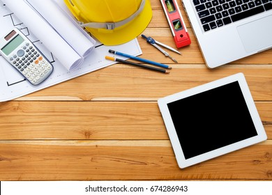 Architect desk project in construction site with blueprint,pen,tablet computer,hardhat,construction level, calculator,laptop and cup of coffee .Top view with copy space.