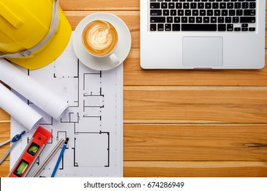 Architect desk project in construction site with blueprint,pen,laptop computer,hardhat,construction level, calculator and cup of coffee .Top view with copy space.