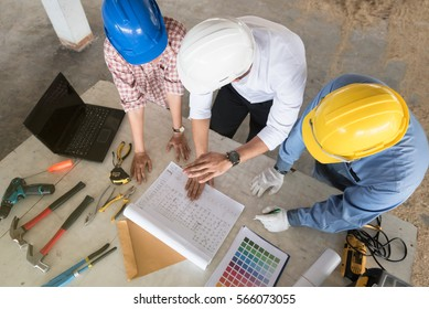 Architect develop a plan house with working tools. Top view of multi-ethnic group of engineers meeting at construction site. Interior design team meeting brainstorming concept.