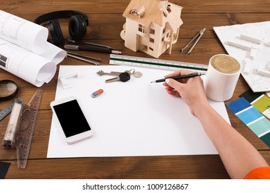 Architect drawing architectural project. Unrecognizable designer hands working with building blueprint, blank smartphone screen, mockup