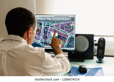 Architect drawing with cad software designing building. Rear view. He is pointing the screen
