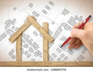Architect drawing a conceptual wooden house over an imaginary cadastral map of territory with buildings, fields and roads - concept image