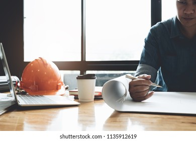 architect drawing on blueprint architectural, Young man working on his plane project at site construction work - Engineering construction  Concept