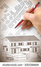 Architect drawing a residential building over an imaginary cadastral map of territory with buildings, fields and roads