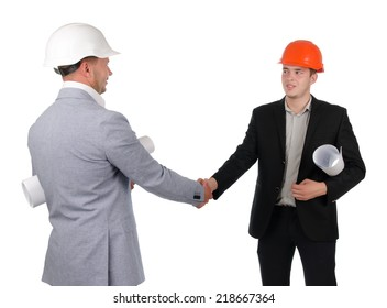 Architect and engineer or builder each wearing a hardhat with a blueprint rolled up under their arms standing shaking hands , on white