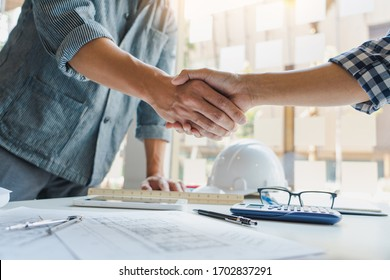 Architect and engineer construction workers shaking hands while working for teamwork and cooperation concept after finish an agreement in the office construction site, success collaboration concept