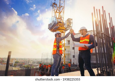 Architect and engineer construction workers shaking hands while working at outdoors construction site. Building construction collaboration concept